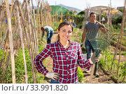 Cheerful Peruvian woman with rake at smallholding garden. Стоковое фото, фотограф Яков Филимонов / Фотобанк Лори