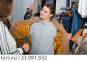 Woman trying new coat in showroom. Стоковое фото, фотограф Яков Филимонов / Фотобанк Лори