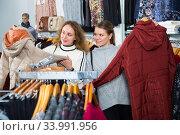 Women choosing new overcoat. Стоковое фото, фотограф Яков Филимонов / Фотобанк Лори
