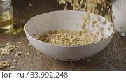 Купить «Woman's hand pours natural granola into ceramic bowl against dar», видеоролик № 33992248, снято 3 июля 2020 г. (c) Ярослав Данильченко / Фотобанк Лори