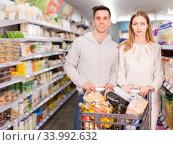 Купить «Cheerful man and woman with shopping cart», фото № 33992632, снято 7 ноября 2019 г. (c) Яков Филимонов / Фотобанк Лори