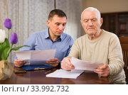 Adult man with elderly father analyzing papers. Стоковое фото, фотограф Яков Филимонов / Фотобанк Лори