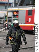 Пожарный возле загоревшегося здания (2020 год). Редакционное фото, фотограф Дмитрий Неумоин / Фотобанк Лори