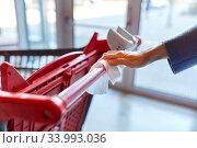 Купить «hand cleaning shopping cart handle with wet wipe», фото № 33993036, снято 30 апреля 2020 г. (c) Syda Productions / Фотобанк Лори