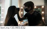 Young woman cosmetologist draws white markup on the eyebrows of a model in the studio. Стоковое видео, видеограф Константин Шишкин / Фотобанк Лори