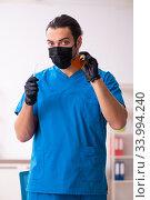 Купить «Young male dentist working in the clinic», фото № 33994240, снято 1 февраля 2020 г. (c) Elnur / Фотобанк Лори