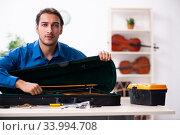 Купить «Young male repairman repairing violin», фото № 33994708, снято 25 октября 2019 г. (c) Elnur / Фотобанк Лори