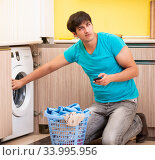 Young husband man doing laundry at home. Стоковое фото, фотограф Elnur / Фотобанк Лори