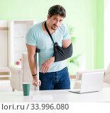 Injured man with crutches sitting at home. Стоковое фото, фотограф Elnur / Фотобанк Лори