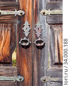 Купить «A close up of old cracked and broken wooden exterior double doors with ornate iron and brass handles keyholes and hinges», фото № 34000188, снято 12 июля 2020 г. (c) easy Fotostock / Фотобанк Лори
