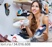 Купить «Portrait of woman looking confused with two pair of shoes», фото № 34016608, снято 7 июля 2020 г. (c) Яков Филимонов / Фотобанк Лори