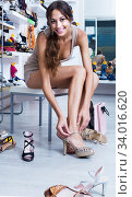 girl customer trying on chosen shoes in footwear department. Стоковое фото, фотограф Яков Филимонов / Фотобанк Лори