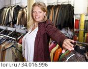 Купить «Woman trying on leather jacket», фото № 34016996, снято 5 сентября 2018 г. (c) Яков Филимонов / Фотобанк Лори