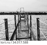 Купить «A perspective view of an abandoned broken rusty iron jetty running into to sea», фото № 34017588, снято 12 июля 2020 г. (c) easy Fotostock / Фотобанк Лори