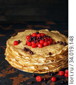 Russian pancakes with berries in front of dark background. Pancake week - the ancient Slavic festival of seeing off the winter. Стоковое фото, фотограф Nataliia Zhekova / Фотобанк Лори