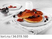 Купить «Healthy summer breakfast, homemade classic american pancakes with fresh berry, nuts and honey, morning light grey stone background», фото № 34019160, снято 3 апреля 2019 г. (c) Nataliia Zhekova / Фотобанк Лори