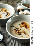 Two bowls with delicious mushroom soup on wooden table. Стоковое фото, фотограф Nataliia Zhekova / Фотобанк Лори