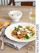 Купить «Mixed vegetable stir fry with mushrooms and cottage cream cheese. Tender mushroom stir fry served in a white plate with white wine and bread on the wooden table. Vegan food», фото № 34019220, снято 28 июня 2019 г. (c) Nataliia Zhekova / Фотобанк Лори