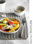 Купить «Mixed vegetable stir fry with parmesan cheese. Roasted vegetables mix on the plate with cutlery on the wicker serving mat, food above. Tender seasonal vegetables stir fry. Vegan food», фото № 34019236, снято 29 июля 2019 г. (c) Nataliia Zhekova / Фотобанк Лори