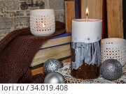 Купить «Decorative pine cones and candles cylindrical shape on textured wooden surface. Handmade candles lit in vintage interior», фото № 34019408, снято 1 декабря 2015 г. (c) Nataliia Zhekova / Фотобанк Лори