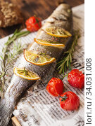 Oven-baked Sea bass with lemon and herbs. fish, baked entirely. Стоковое фото, фотограф Nataliia Zhekova / Фотобанк Лори