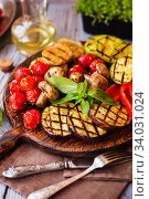 Grilled vegetables on cutting board on wooden background. Стоковое фото, фотограф Nataliia Zhekova / Фотобанк Лори