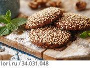 Купить «Chocolate cookies with sesame seeds on the wooden board.», фото № 34031048, снято 22 марта 2019 г. (c) Nataliia Zhekova / Фотобанк Лори
