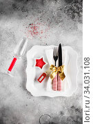Купить «Christmas table place setting with square plate, cutlery with festive decorations gold ribbon, bauble red telephone box, star-shaped bowl with red sugar. Christmas Xmas New Year holiday backdrop», фото № 34031108, снято 12 ноября 2019 г. (c) Nataliia Zhekova / Фотобанк Лори