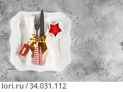 Christmas table place setting with square plate, cutlery with festive decorations gold ribbon, bauble red telephone box, star-shaped bowl with red sugar. Christmas Xmas New Year holiday. Стоковое фото, фотограф Nataliia Zhekova / Фотобанк Лори