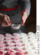process of making marshmallow. Close up hands of the chef with metal sieve sprinkling zephyr with Powdered sugar at pastry shop kitchen. confectioner sprinkles sugar powder confectionery. Стоковое фото, фотограф Nataliia Zhekova / Фотобанк Лори