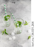 Купить «glasses of cold water with fresh mint leaves and ice cubes on grey concrete background», фото № 34031264, снято 4 июня 2019 г. (c) Nataliia Zhekova / Фотобанк Лори