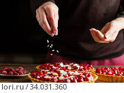 Beautiful freshly made cherry tart decorated with almond chips. Process of making tart. Close up hands of the chef sprinkling cake with almond chips at pastry shop kitchen. Стоковое фото, фотограф Nataliia Zhekova / Фотобанк Лори