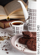 Still life composition of chocolate cookies on the plate, coffee cup, coffee pot and books. Стоковое фото, фотограф Nataliia Zhekova / Фотобанк Лори