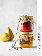 Купить «two jars of fruit homemade jam. pear marmalade with coffee beans and Jar of blood orange jam», фото № 34031680, снято 23 апреля 2019 г. (c) Nataliia Zhekova / Фотобанк Лори