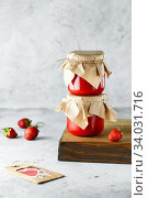 Homemade strawberry jam in glass jar on the wooden box on the gray background. Wild strawberry jam in swing-top jar on wood with strawberries in the back. Food photography. Seasonal cooking. Стоковое фото, фотограф Nataliia Zhekova / Фотобанк Лори