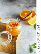Homemade orange jam in glass jar on the wooden box on the gray background. Orange jam in swing-top jar on wood with orange slices in the back. Food photography. Seasonal cooking. Стоковое фото, фотограф Nataliia Zhekova / Фотобанк Лори