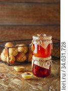 Купить «Apricot jam on a wooden rustic background. Two jars of fruit homemade marmalade. Glass jars with different kinds of jam», фото № 34031728, снято 17 июля 2019 г. (c) Nataliia Zhekova / Фотобанк Лори