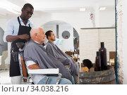 African barber putting on hairdresser cape to elderly client. Стоковое фото, фотограф Яков Филимонов / Фотобанк Лори