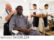 African man getting haircut from elderly barber. Стоковое фото, фотограф Яков Филимонов / Фотобанк Лори