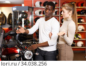 Portrait of joyous man and woman looking new motorbike at motosalon showroom. Стоковое фото, фотограф Яков Филимонов / Фотобанк Лори