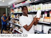 Focused muscular African man choosing sports nutrition products in shop, reading content label. Стоковое фото, фотограф Яков Филимонов / Фотобанк Лори