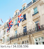 Купить «British flags flying on the balcony of a building in central London», фото № 34038596, снято 20 августа 2017 г. (c) Nataliia Zhekova / Фотобанк Лори