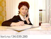 Женщина-администратор гостиницы говорит по телефону и заполняет журнал за стойкой. Стоковое фото, фотограф Ирина Борсученко / Фотобанк Лори