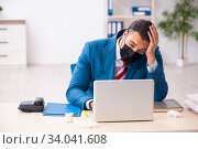 Купить «Sick male employee suffering at workplace from coronavirus», фото № 34041608, снято 15 февраля 2020 г. (c) Elnur / Фотобанк Лори