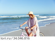Купить «Caucasian woman spending time seaside and riding a bike», фото № 34046816, снято 25 февраля 2020 г. (c) Wavebreak Media / Фотобанк Лори