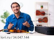 Купить «Young male repairman repairing violin», фото № 34047144, снято 25 октября 2019 г. (c) Elnur / Фотобанк Лори