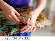 Купить «The girl artist holding a palette with oil paints, brush and palette knife», фото № 34047332, снято 27 марта 2016 г. (c) Nataliia Zhekova / Фотобанк Лори