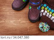 Купить «Winter children's boots and hat on the wooden textured background», фото № 34047380, снято 19 октября 2015 г. (c) Nataliia Zhekova / Фотобанк Лори