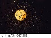 Купить «Drops of rain and light of the moon on dark glass at night. Wet window glass with lots of rain drops and a view of the night blac sky with the yellow gold glowing moon.», фото № 34047388, снято 11 февраля 2020 г. (c) Nataliia Zhekova / Фотобанк Лори