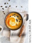 Купить «Pumpkin cream soup. Roasted pumpkin and carrot puree soup with turmeric, cream, paprica, chives and pumpkin seeds on grey background. Vegetarian and Vegan recipe. Green living. Organic food.», фото № 34047424, снято 25 апреля 2020 г. (c) Nataliia Zhekova / Фотобанк Лори